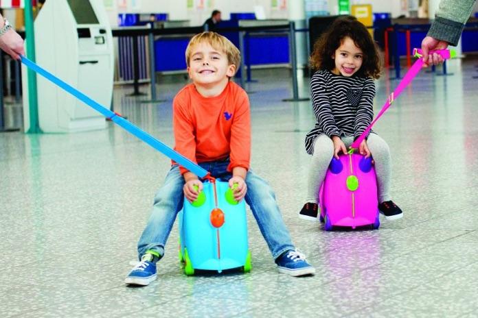 la valigia trunki con i bambini in sella